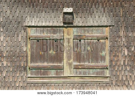 Closed window with hearts of a traditional norwegian wooden house