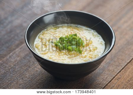 Congee bowl on wooden table background.