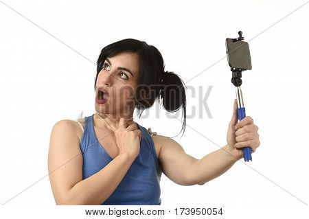 young attractive and sexy woman taking selfie photo with stick and mobile phone camera posing happy and playful isolated on white background in shooting self portrait concept