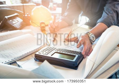 Close up hand of civil engineer people with drawing blueprint and using calculator for design and planning to budget