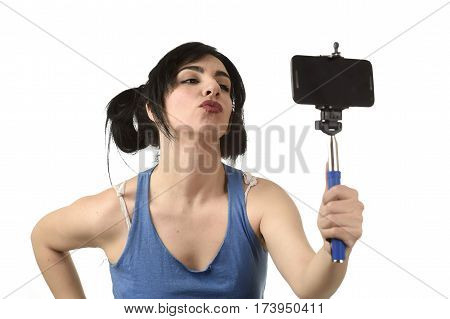 young attractive and sexy woman taking selfie photo with stick and mobile phone camera posing happy and playful sending kiss isolated on white background in shooting self portrait