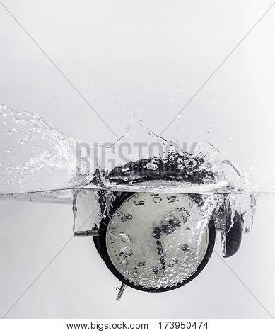 Drowning clock in the water with a splash.