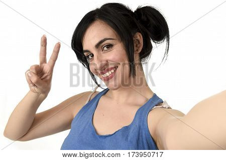 young attractive and sexy woman taking selfie photo with stick and mobile phone camera posing happy and playful peace sign isolated on white background in shooting self portrait