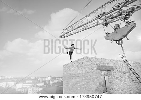 Perfect balance Monochrome shot of a muscular athletic man dressed in vintage outfit balancing on one leg on the edge of a building construction builder balance fearless athlete retro copyspace.