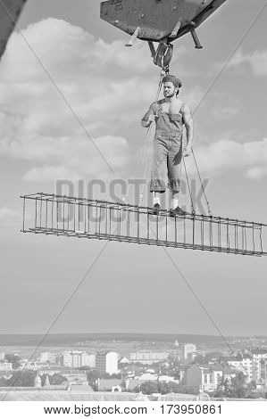 Looking around. Vertical monochrome shot of a professional builder posing on a crossbar hanging from a construction crane profession job working retro vintage industry development business concept