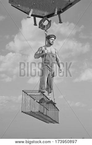 Higher heights. Black and white shot of a handsome muscular construction worker looking away standing on a crossbar at construction area professional handyman building developer confidence concept