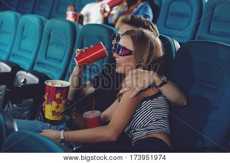Side view of two friends embracing and sitting in modern cinema hall, watching funny movie. Positive couple of caucasian spending free time in cinema.
