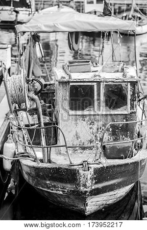 Old heavy used fishing boat close up in a marine dock.