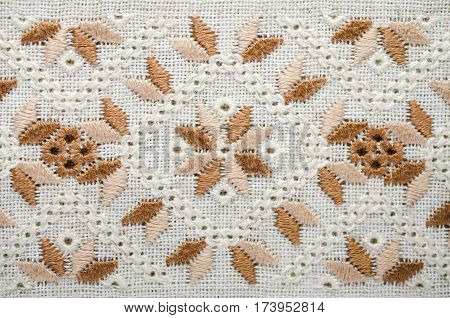 Background with embroidery. Embroidery pattern brown and beige for background or cover. Geometric ornament.