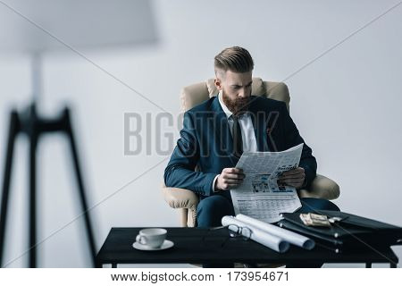 portrait of concentrated businessman reading newspaper in office