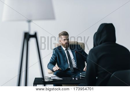Young bearded businessman talking with anonymous person in black hood