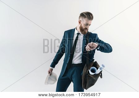 Stylish businessman with blueprints in shoulder bag checking wristwatch