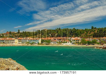 The Rocky Coast   Overlooking The Turquoise Blue And Green Sea  And Village In Warm Summer Day.