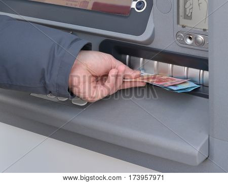 Close-up of hand of man to withdraw money from an ATM