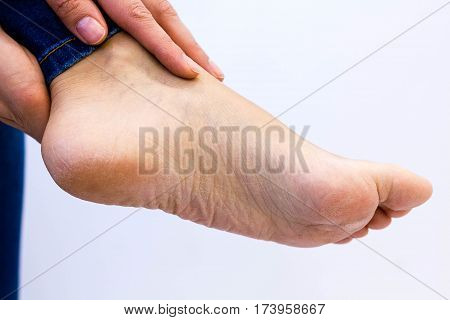 woman checks her aching foot. Closeup of pregnant woman hands doing foot massage. Wrinkled hands toching a naked aching foot. Pain in the foot.
