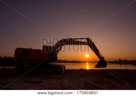 Backhoe was digging earthmoving work at construction site on sunset background