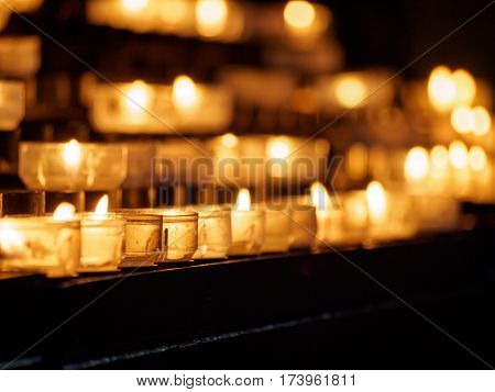 Close-up macro detail of multiple candles in glass candle holders in multiple rows and heights. Peace and religion concept.