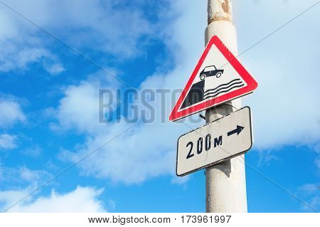 Road signs on lamppost in Russia - unprotected quayside or riverbank and sign pointer of distance to the object.