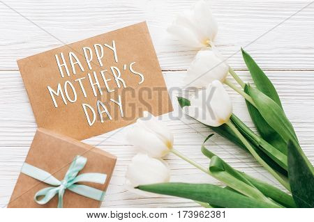 Happy Mothers Day Text Sign On Stylish Craft Present With Greeting Card And Tulips On White Wooden R