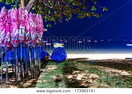 PATTAYA THAILAND - JANUARY 17: This is Pattaya beach at night which is the main beach in the center of Pattaya with umbrellas and boats in the background January 17 2017 in Pattaya
