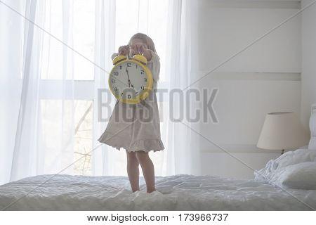 Portrait of little girl holdinga huge alarm clock, isolated over white