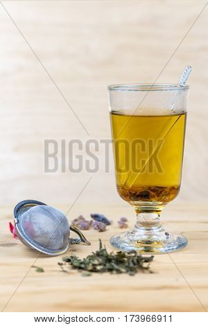 Hot steaming herbal tea in a glass mug with dried leaves and a strainer for steeping the brew in the foreground