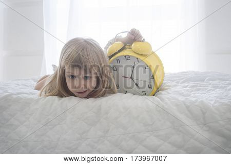 Close-up portrait of funny little girl with huge yellow alarm clock over white background