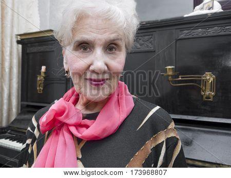 Senior female musician posing next to the retro piano indoor cropped portrait