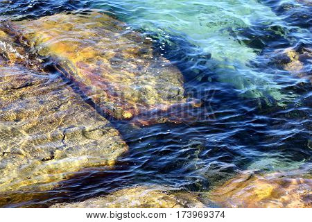 Large beige rocks just under the surface of the water, blue