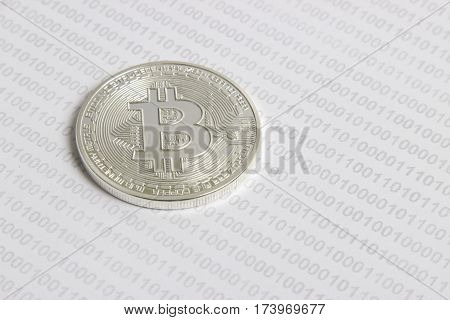 silver bitcoin on the background of binary code