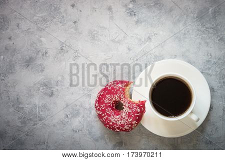 Bitten pink donut and cup of coffee at concrete table. Top view with copy space.
