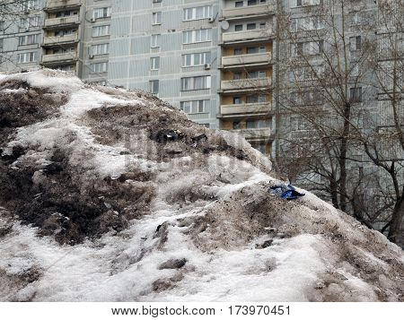 big mountain of dirty melting snow and debris on the background high-rise buildings in the city