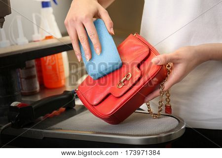 Dry cleaning business concept. Woman washing bag with sponge