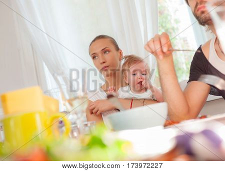 A little baby boy is held by his mother in restaurant during a family lunch.