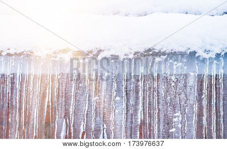 icicles hanging on the cornice on the wall background