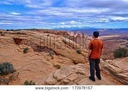 Man hiker on cliff looking at canyon views. Mesa Arch in Canyonlands National Park. La Sal Mountains. Moab. Cedar City. Utah. United States.