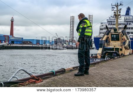 IJMUIDEN, NETHERLANDS - AUGUST 16 2015 : Police man checking the borders of the Ijmuiden harbour