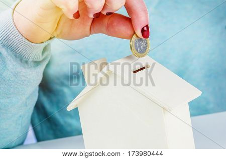 Woman inserting a euro coin into a wooden money box