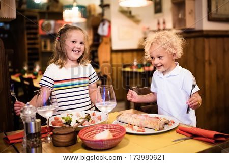 Kids Eating Pizza In Italian Restaurant