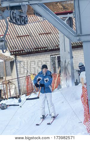 young man in jacket with ski and lift