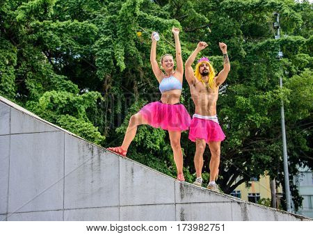 RIO DE JANEIRO, BRAZIL - FEBRUARY 28, 2017: Two persons, male and female, in bright pink tutu skirts standing at the Memorial Getulio Vargas, Gloria neighborhood at Carnaval 2017
