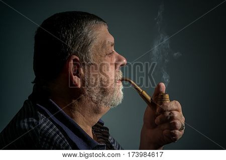 Film toned portrait of Caucasian bearded man smoking tobacco pipe against dark background