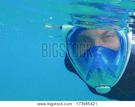 Woman in mask in blue water. Snorkeling girl in full face mask. Blue sea water banner template with place for text. Underwater photo of female snorkeling person. Portrait in mask under sea surface