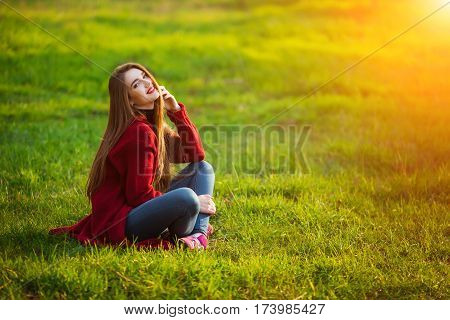 Happy young woman. Beautiful female with long healthy hair enjoying sun light in park sitting on green grass. Spring, autumn portrait