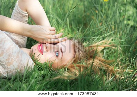 Cute Blue-eyed Blonde Lying on the Spring Grass. Happy young Woman with Red Lips and Natural Make Up in White Lacy Dress Having Fun in Spring Garden.