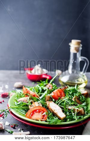Healthy food: grilled chicken and mix salad of tomatoes, collard greens and lettuce on a plate with olive oil