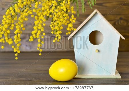 Easter egg, birdhouse and mimosa flower on wooden background