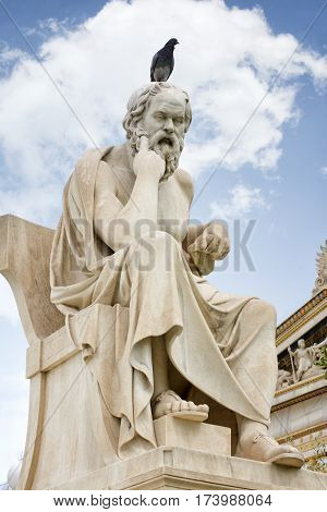 ATHENS, GREECE, SEPTEMBER 8, 2016: Statue of  Socrates with a bird standing on his head at Academy Of Athens, Greece's national academy, and the highest research establishment in the country.