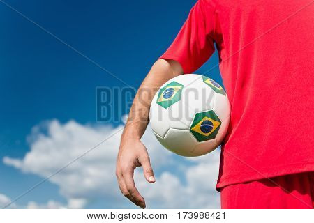 Soccer player holding Brazil ball toned image, horizontal image, selective focus