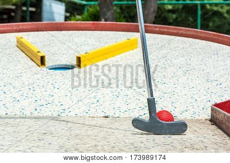 Closeup of club hitting golf ball. Game of miniature golf.